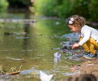 a photograph of a young girl playing beside a creek
