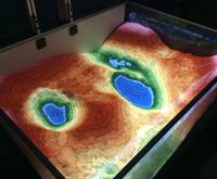 A photo of an augmented reality sandbox. Different elevations are indicated by different colours in the sanbox.