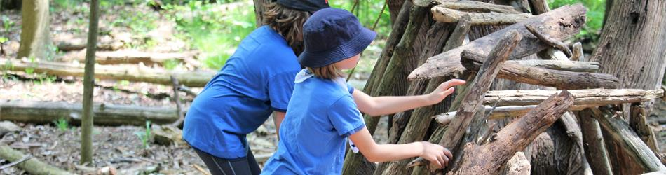 Two young girls in blue t-shirts are working to built a large shelter with logs and sticks.