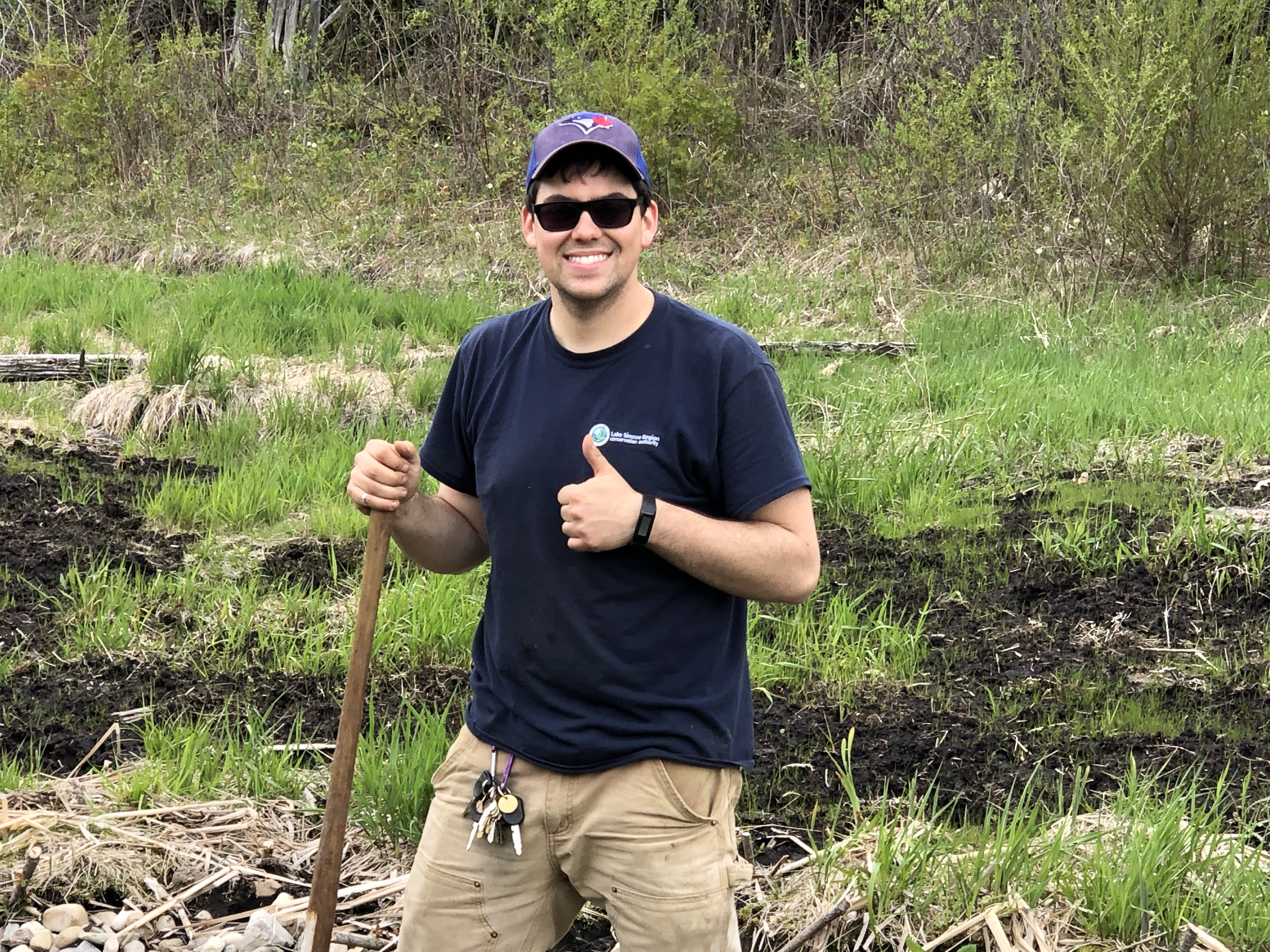 Cory Byron looks at the camera. He's smiling, holding a shovel and with one hand giving thumbs up.