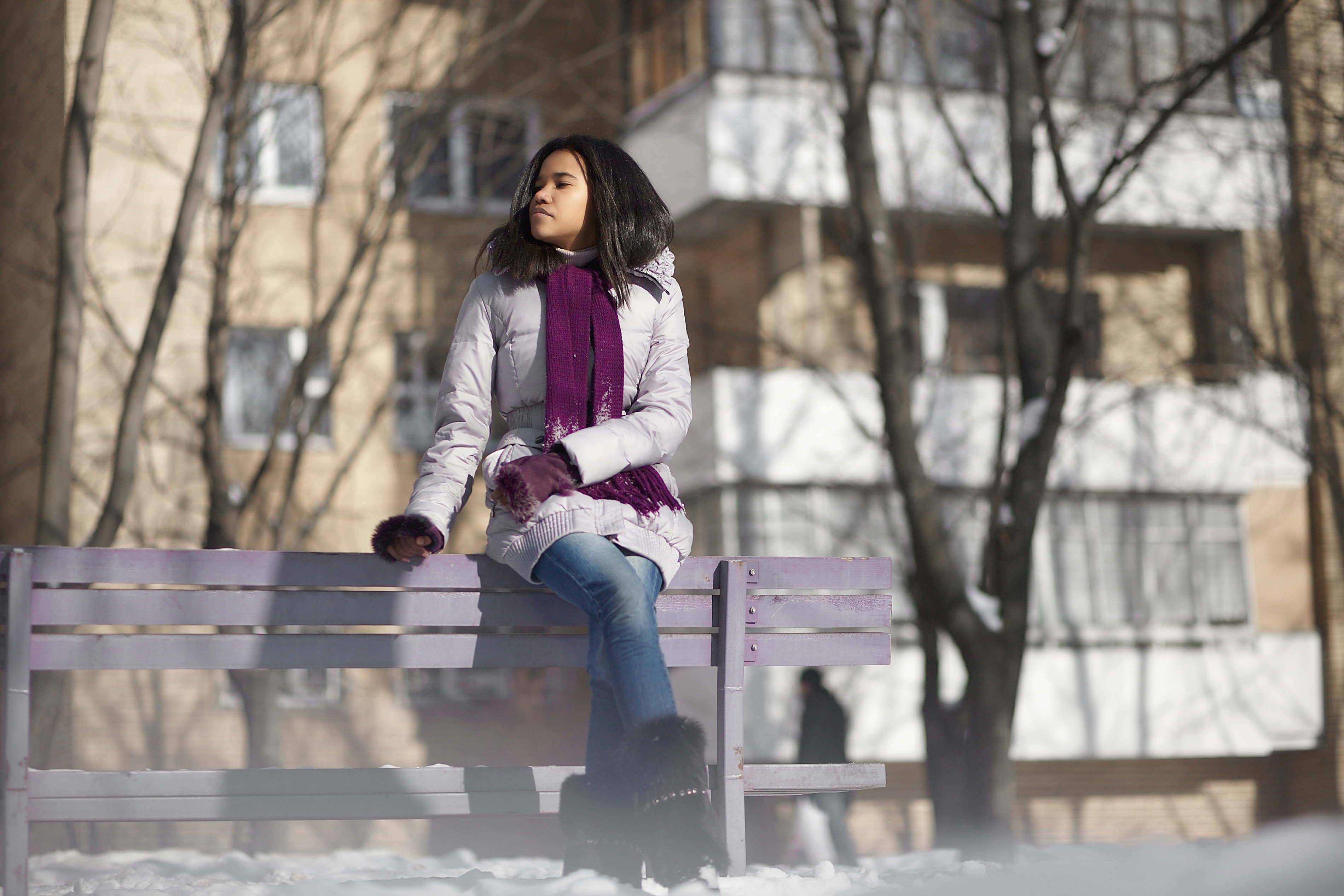 A woman dressed in a winter jacket and scarf, sitting on a park bench.