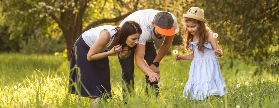 Two adults and a girl looking at dandelion fluff in a field.