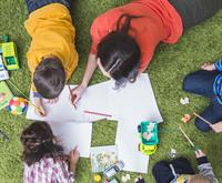 An aerial view of a family laying in the grass and colouring.