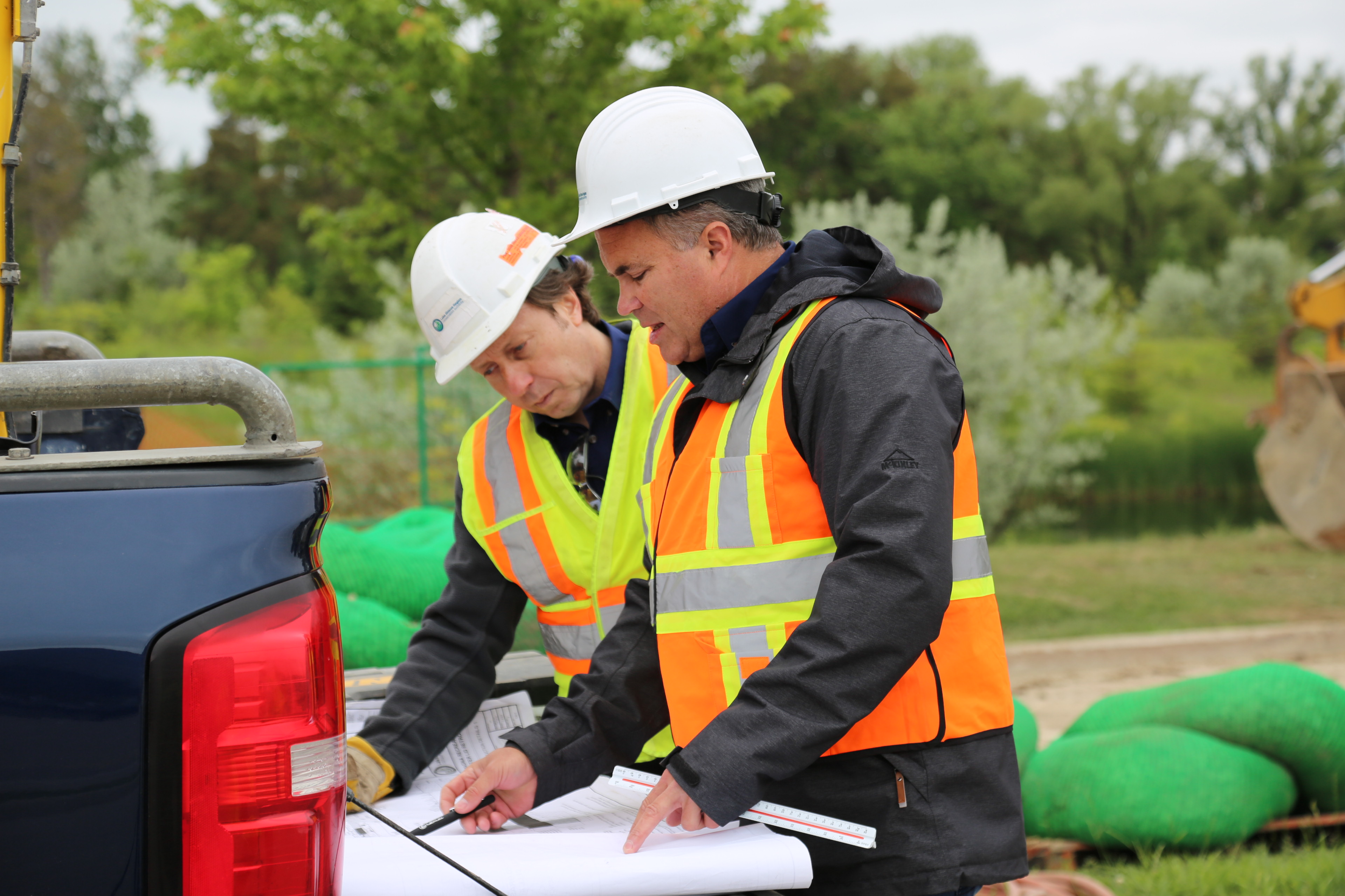 Two men wearing construction hats and vests looking at site plans.