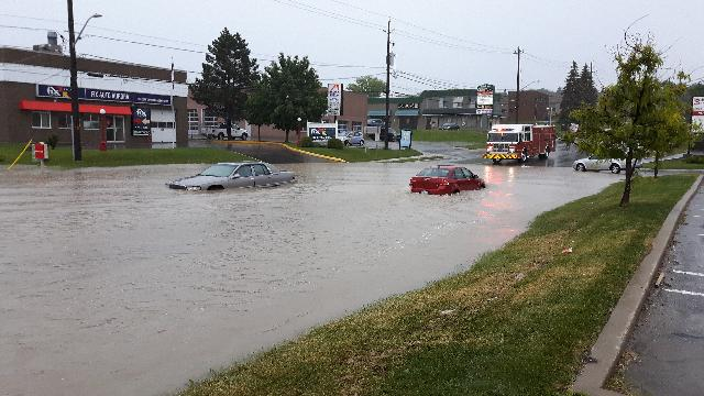 A picture of a flooded road in Aurora. Cars can be seen floating in the water. The road is blocked by a firetruck.