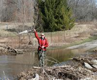 A photo of a woman standing in a creek preparing to take a sample with a net