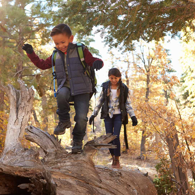 Two children walking on a log and smiling.