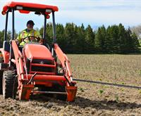 a photograph of a tree planting tractor on a field during a full service tree planting. Seedlings can be seen on the ground.